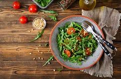 żywienioniowy menu Weganin kuchnia Zdrowa sałatka z arugula, pomidorami i sosnowymi dokrętkami, zdjęcie royalty free