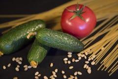 Żywienioniowy sklep spożywczy ustawiający trzy zielonego ogórka, jeden dojrzały czerwony Tom Fotografia Stock