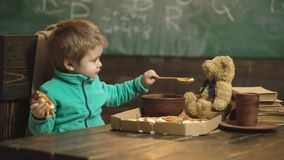 Żywieniowy pojęcie Małe dziecko żywieniowy miś w szkole Chłopiec karmienie i brać opieka zabawkarski przyjaciel w sala lekcyjnej zbiory