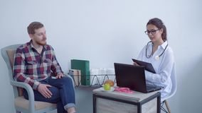 Żywiona konsultacja, dietician żeński spectacled radzi klient samiec i poleca żywienioniowych nadprogramy dla zbiory wideo