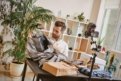Żywy lać się Młodego męskiego mody blogger wideo magnetofonowy przegląd o klasycznej pelerynie na cyfrowej kamerze w domu obraz stock