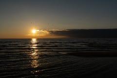 Żywy zmierzch z bardzo niskim słońcem na morzu bałtyckim Tuja Latvia, Kwiecień, - 13, 2019 - Czerwoni kolory - zdjęcie stock