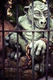 Άγαλμα τεράτων πίσω από τα κάγκελα στον κήπο στοκ φωτογραφίες