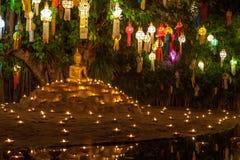 Άγαλμα του Βούδα που περιβάλλεται από τα κεριά και ζωηρόχρωμο Στοκ φωτογραφία με δικαίωμα ελεύθερης χρήσης