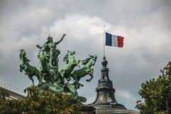 Άγαλμα χαλκού και γαλλική σημαία που εξωραΐζουν τη μεγάλη κορυφή κτηρίου Palais σε μια νεφελώδη ημέρα στο Παρίσι Στοκ Εικόνες