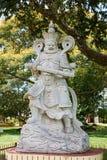 Άγαλμα sohei του Βούδα πολεμιστών μνημείων αγαλμάτων με το πράσινο υπόβαθρο δέντρων με τα κίτρινα λουλούδια στοκ φωτογραφία