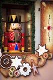 Άγαλμα καρυοθραύστης στρατιωτών που στέκεται μπροστά από ένα διακοσμημένο παράθυρο Χριστουγέννων Στοκ εικόνες με δικαίωμα ελεύθερης χρήσης