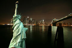 Άγαλμα της ελευθερίας ενάντια στην πόλη της Νέας Υόρκης νύχτας, ΗΠΑ Στοκ εικόνες με δικαίωμα ελεύθερης χρήσης