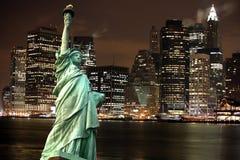 Άγαλμα της ελευθερίας ενάντια στην πόλη της Νέας Υόρκης νύχτας, ΗΠΑ Στοκ Εικόνες