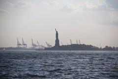 Άγαλμα της ελευθερίας στο νησί κατά την άποψη σκιαγραφιών από το Μανχάταν Στοκ εικόνες με δικαίωμα ελεύθερης χρήσης