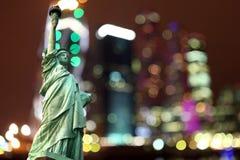 Άγαλμα της Νέας Υόρκης της ελευθερίας ενάντια στην πόλη νύχτας Στοκ εικόνα με δικαίωμα ελεύθερης χρήσης