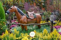 Άγαλμα του αλόγου στον τομέα των λουλουδιών Στοκ Εικόνα