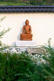 Άγαλμα του Βούδα μεταξύ των πράσινων κλάδων σε έναν κήπο των πετρών στοκ φωτογραφίες με δικαίωμα ελεύθερης χρήσης