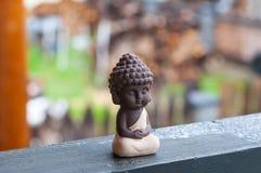 Άγαλμα του μωρού Βούδας - ειρηνικό μυαλό Προσεηθείτε τη θεότητα στο υπόβαθρο θαμπάδων Έννοια Meditate στοκ φωτογραφία