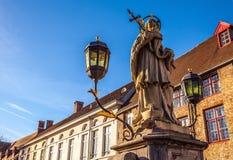 Άγαλμα του ST John Nepomuk στη γέφυρα παλαιά κόκκινα πόλης Windows λουλουδιών πορτών οικοδόμησης του Βελγίου Μπρυζ Στοκ Φωτογραφίες