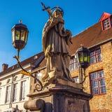 Άγαλμα του ST John Nepomuk στη γέφυρα παλαιά κόκκινα πόλης Windows λουλουδιών πορτών οικοδόμησης του Βελγίου Μπρυζ Στοκ Εικόνες