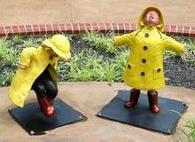 Άγαλμα δύο μικρών παιδιών που καταβρέχουν και που βαδίζουν βαριά στη βροχή Στοκ Εικόνα