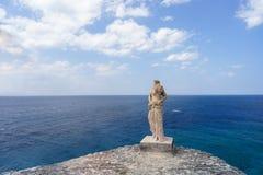Άγαλμα Grecian από την πλευρά απότομων βράχων στο νησί τύχης στοκ φωτογραφία με δικαίωμα ελεύθερης χρήσης