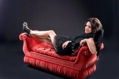 άγγελος ως σκοτεινό ντυμένο κόκκινο καναπέ κοριτσιών Στοκ φωτογραφία με δικαίωμα ελεύθερης χρήσης