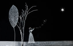 Άγγελος που εξετάζει επάνω το αστέρι Χριστουγέννων στοκ εικόνα με δικαίωμα ελεύθερης χρήσης