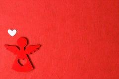 Άγγελος Χριστουγέννων σε ένα κόκκινο υπόβαθρο, ξύλινη διακόσμηση eco, παιχνίδι Στοκ Φωτογραφίες