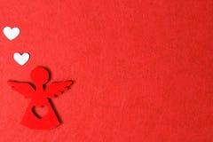 Άγγελος Χριστουγέννων σε ένα κόκκινο υπόβαθρο, ξύλινη διακόσμηση eco, παιχνίδι Στοκ Εικόνες