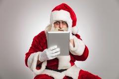 Άγιος Βασίλης διαβάζει κάτι που συγκλονίζει στην ταμπλέτα του Στοκ φωτογραφία με δικαίωμα ελεύθερης χρήσης