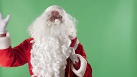 Άγιος Βασίλης εισάγει το πλαίσιο με μια τσάντα, εξετάζει τη κάμερα και κυματισμός του χεριού του, που χαιρετά το πράσινο chromake φιλμ μικρού μήκους