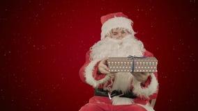 Άγιος Βασίλης: Εύθυμα δώρα στο κόκκινο υπόβαθρο με το χιόνι Στοκ φωτογραφία με δικαίωμα ελεύθερης χρήσης