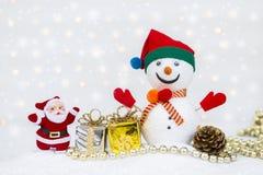 Άγιος Βασίλης και άτομο χιονιού με το ασημένιο και χρυσό κιβώτιο δώρων πέρα από θολωμένος bokeh στοκ φωτογραφία