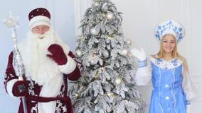 Άγιος Βασίλης και κορίτσι χιονιού με ένα δώρο κοντά στο χριστουγεννιάτικο δέντρο του νέου έτους φιλμ μικρού μήκους