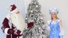 Άγιος Βασίλης και κορίτσι χιονιού με ένα δώρο κοντά στο χριστουγεννιάτικο δέντρο του νέου έτους απόθεμα βίντεο