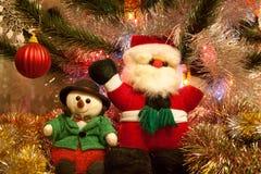 Άγιος Βασίλης και ο χιονάνθρωπος στέκονται κοντά στο διακοσμημένο χριστουγεννιάτικο δέντρο Στοκ Φωτογραφίες