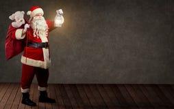 Άγιος Βασίλης με μια τσάντα και έναν λαμπτήρα Χριστουγέννων Στοκ Εικόνες