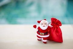 Άγιος Βασίλης με την κόκκινη τσάντα δώρων πέρα από το θολωμένο μπλε υπόβαθρο στοκ φωτογραφίες