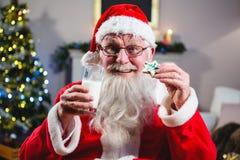 Άγιος Βασίλης που έχει το μπισκότο Χριστουγέννων με ένα ποτήρι του γάλακτος Στοκ Εικόνα
