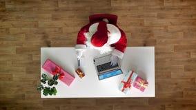 Άγιος Βασίλης που εργάζεται στο γραφείο στο lap-top, δακτυλογράφηση, εναέρια άποψη, κορυφή κάτω από τον πυροβολισμό, γράφει το κε απόθεμα βίντεο