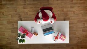Άγιος Βασίλης που εργάζεται στο γραφείο στο lap-top, μουσική ακούσματος στα ακουστικά, δακτυλογράφηση, εναέρια άποψη, κορυφή κάτω φιλμ μικρού μήκους