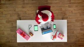 Άγιος Βασίλης που εργάζεται στο γραφείο στο lap-top, το smartphone και την ταμπλέτα με το chromakey, πράσινη οθόνη, δακτυλογράφησ φιλμ μικρού μήκους