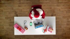 Άγιος Βασίλης που εργάζεται στο γραφείο στο lap-top, smartphone με το chromakey, πράσινη οθόνη, δακτυλογράφηση, εναέρια άποψη, κο απόθεμα βίντεο