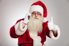 Άγιος Βασίλης που μιλά στο τηλέφωνο κάνει το εντάξει σημάδι Στοκ φωτογραφία με δικαίωμα ελεύθερης χρήσης