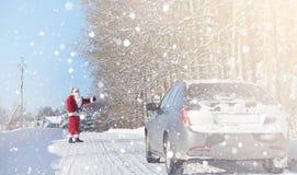 Άγιος Βασίλης προέρχεται με τα δώρα από τον υπαίθριο Santa σε ένα κόκκινο SU Στοκ Εικόνες