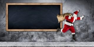 Άγιος Βασίλης σε μια βιασύνη με το σύνολο τσαντών παρουσιάζει το τρέχοντας άλμα στοκ φωτογραφία