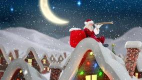 Άγιος Βασίλης σε μια στέγη ενός διακοσμημένου σπιτιού στο χειμερινό τοπίο συνδύασε με το μειωμένο χιόνι ελεύθερη απεικόνιση δικαιώματος