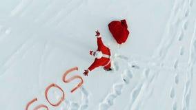 Άγιος Βασίλης στο χιόνι με ένα SOS-σημάδι που γράφεται δίπλα σε τον απόθεμα βίντεο