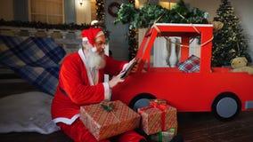 Άγιος Βασίλης συντάσσει τον κατάλογο παρουσιάζει τη χρησιμοποίηση της ταμπλέτας απόθεμα βίντεο