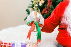 Άγιος Βασίλης φόρεσε γάντια στα χέρια κρατώντας το κιβώτιο δώρων στο δωμάτιο Στοκ φωτογραφίες με δικαίωμα ελεύθερης χρήσης