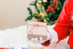 Άγιος Βασίλης φόρεσε γάντια στα χέρια κρατώντας το κιβώτιο δώρων στο δωμάτιο Άγιος Βασίλης έφερε τα δώρα για τα Χριστούγεννα και  Στοκ εικόνες με δικαίωμα ελεύθερης χρήσης