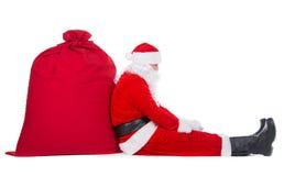 Άγιος Βασίλης κάθεται κουρασμένος κοντά στο μεγάλο κόκκινο σύνολο σάκων Χριστουγέννων παρουσιάζει απομονωμένος στο άσπρο υπόβαθρο Στοκ εικόνες με δικαίωμα ελεύθερης χρήσης