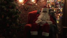 Άγιος Βασίλης κάθεται σε μια καρέκλα στο χριστουγεννιάτικο δέντρο απόθεμα βίντεο
